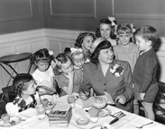 Betty MacDonald signing book with eight children watching.